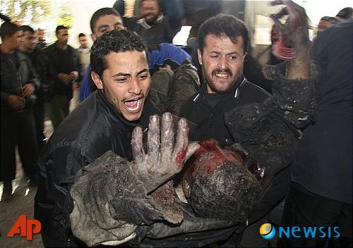 28日(現地時間)、パレスチナ人たちがイスラエル軍の攻撃で重傷を負った男... イスラエル、ガザ